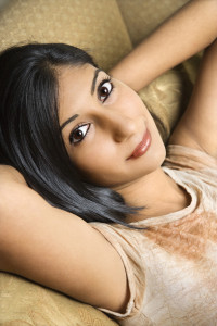 Close up portrait of Asian/Indian young woman leaning back on sofa looking at viewer.