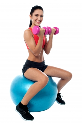 """Fit Woman In Gym Working Out With Dumbbells"" by stockimages"