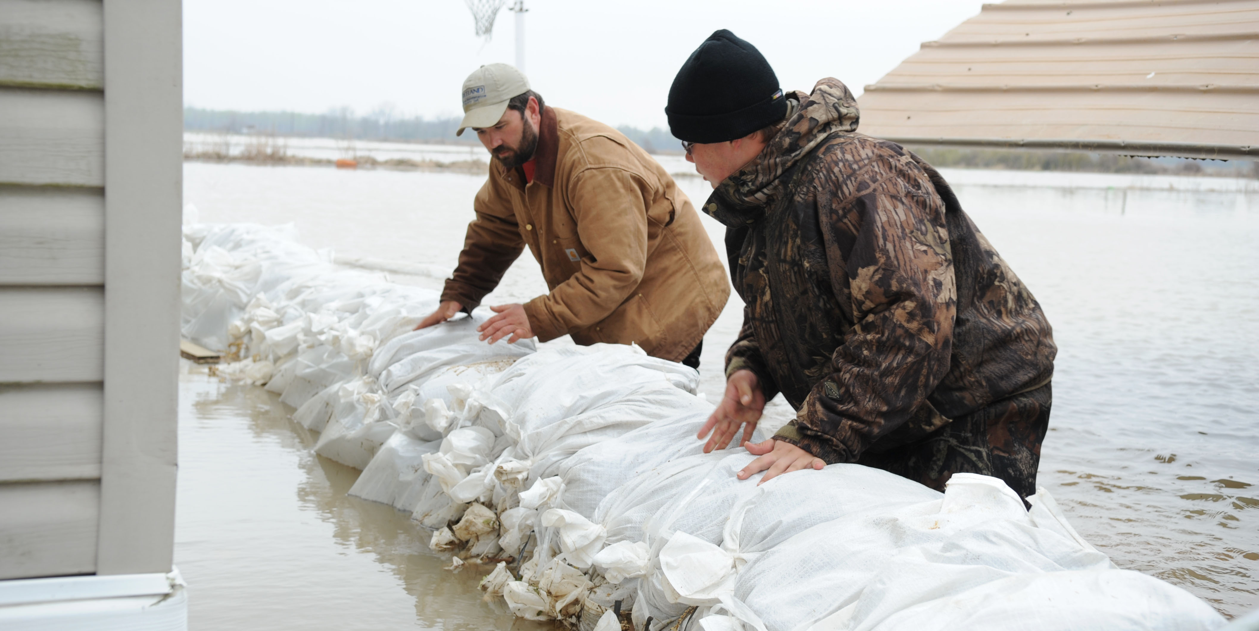 Biscoe, AR-Philip Lightsey, left, and his son Josh, check the water levels around the sandbags which encompass his house.  The sandbags are helping to form a protective barrier so that the water level does not rise and get inside of the house. Jocelyn Augustino/FEMA
