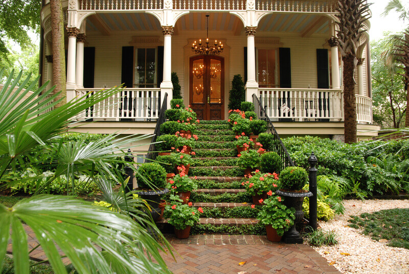 beautiful-front-stairs-and-yard-of-historic-colonial-home-with-flowers-and-ivy